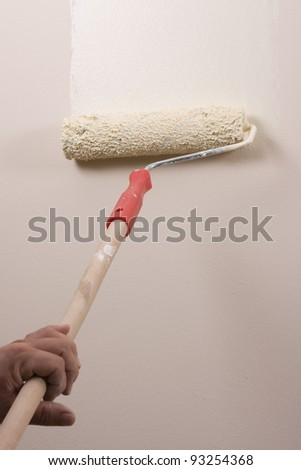 house painter using a paint roller, painting a wall in motion - stock photo