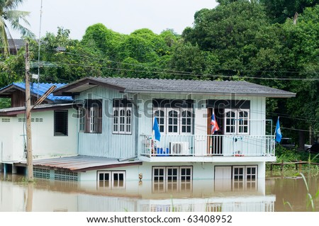 House partly submerged in water during the monsoon season in Thailand. - stock photo