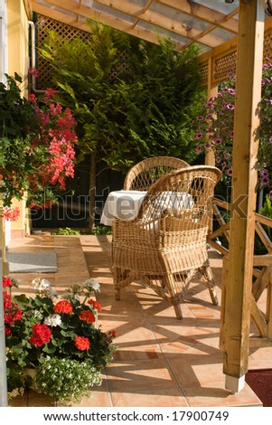 House patio with natural wooden patio furniture - stock photo