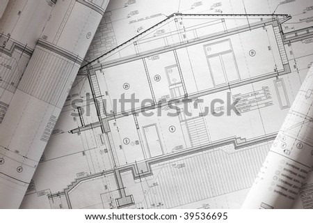 House plan blueprints roled up over table - stock photo