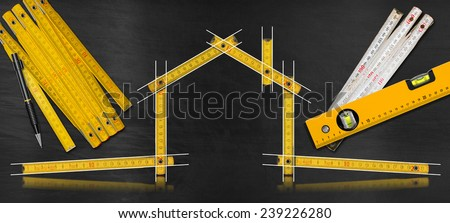 House Project - Yellow Wooden Meter. House project concept. Wooden meter ruler in the shape of house with drawing, propelling pencil, two meter tools and spirit level on a blackboard - stock photo