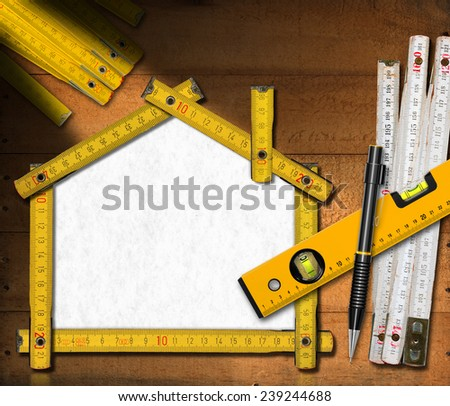 House Project - Yellow Wooden Meter. House project concept. Wooden meter ruler in the shape of house with propelling pencil and spirit level on wooden background - stock photo