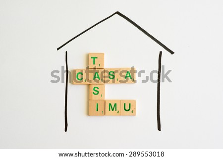 House property tax concept for Italy; wooden letters composing italian wording taxes in local language - stock photo