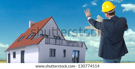 House rendering on a field and an architect with blueprints - stock photo