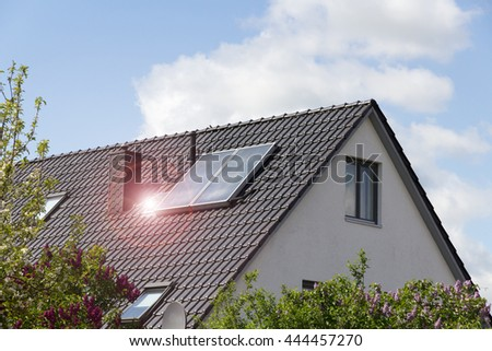 house roof with solar panel and lens flare with blue cloudy sky - stock photo