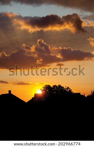 House roofs at sunset with beautiful sky - stock photo