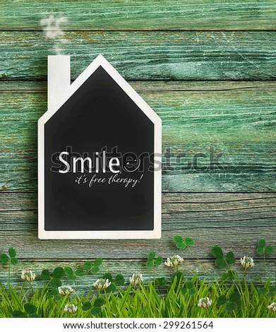 House shaped chalkboard on wood background - stock photo