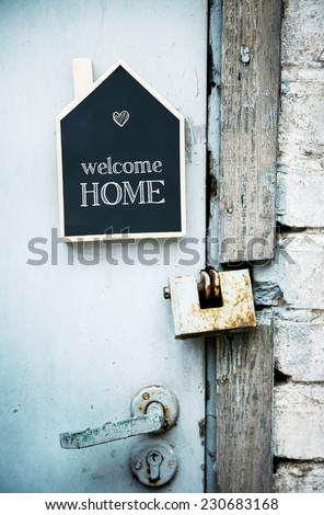 House Shaped Chalkboard sign on rustic blue door WELCOME HOME - stock photo
