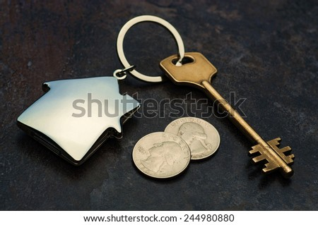 House shaped key-chain with key and coins - stock photo