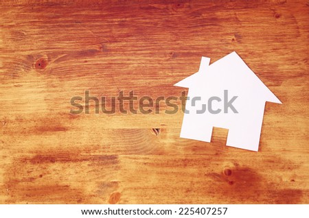 house shaped paper cut over wooden table. room for text