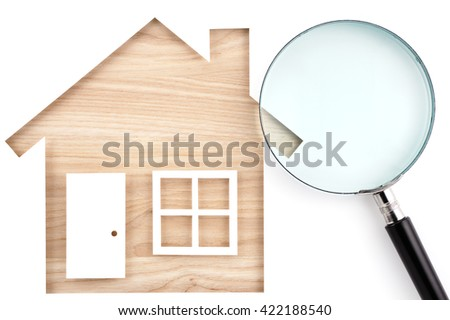 House shaped paper cutout and magnifier on natural wood lumber. Isolated on white background.  - stock photo