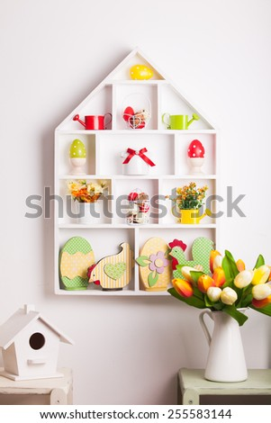House shelves on a wall - Easter decorations for holiday - stock photo