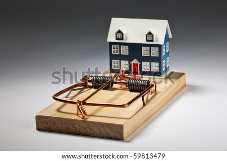House sitting on large mouse trap - luring investors and home owners