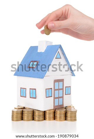House standing on heap of coins isolated on white