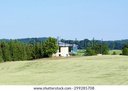 House standing on the edge of the forest with blue sky - stock photo