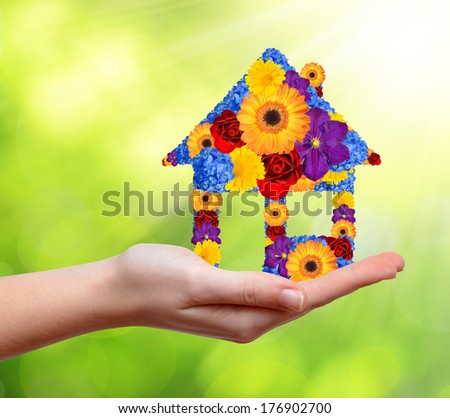 House symbol from flowers in hand - stock photo