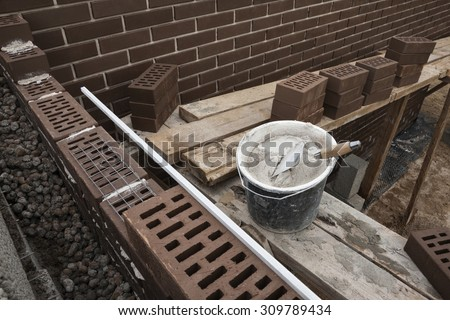 House under construction. Masonry cement and brown clinker bricks at scaffolding boards. - stock photo
