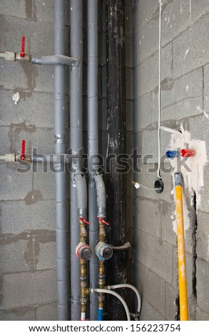 house under construction: pipes and meters in bathroom - stock photo