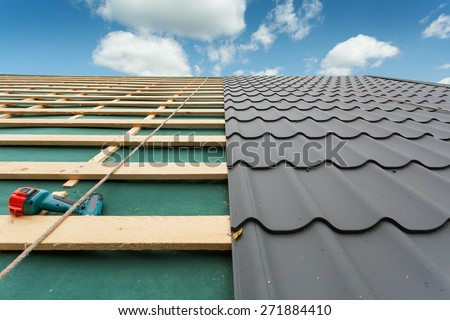 House under construction.Roof  with metal tile,screwdriver and roofing iron - stock photo