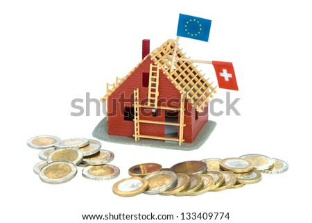 House under construction with Euro coins around it - stock photo