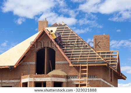 House under construction. Workesr installing fibreboard on the roof - stock photo