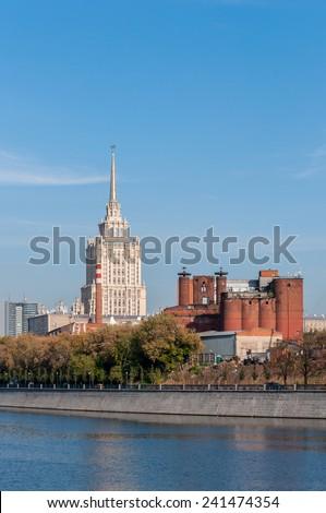 House with a spire Soviet times and industrial building construction. Moskva River embankment. Moscow, Russian Federation - stock photo