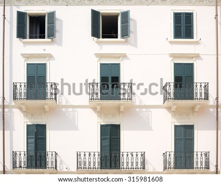 House with balconies and balcony railings with doors - stock photo