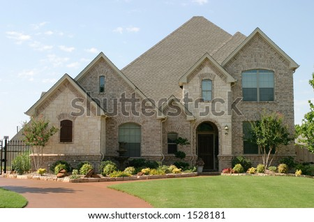 house with beautiful mixture of light colored and white stone and brick; arched windows and entryway. - stock photo