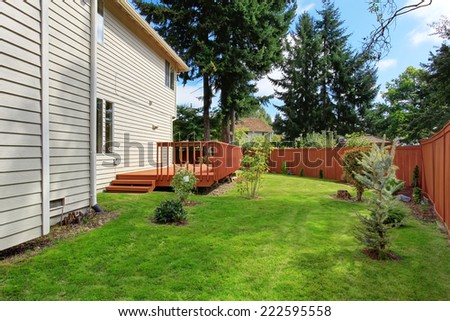 House with brown walkout deck and wooden fence. Backyard landscape with lawn - stock photo