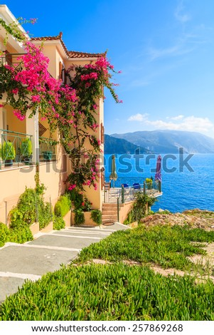 House with flowers along walkway to beach on coast of Kefalonia island in Assos village, Greece - stock photo