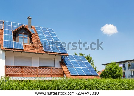 House with garden and solar panels on the roof - stock photo