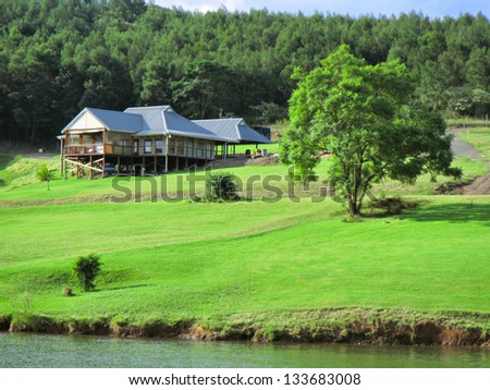 House with lawn on lake shore. Shot in Albert Falls Dam Nature Reserve, Kwazulu-Natal, South Africa - stock photo
