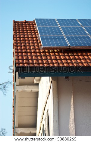 house with solar panels installed with blue sky in the background - stock photo