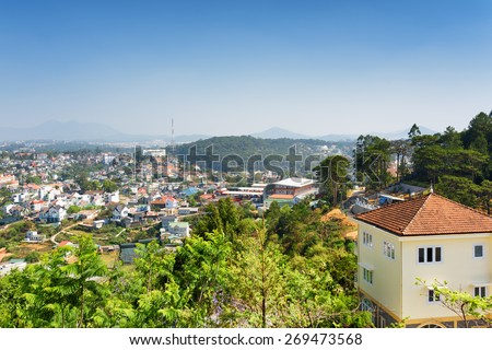 House with tile roof and a beautiful view of Da Lat city (Dalat) on the blue sky background in Vietnam. Da Lat is a popular tourist destination of Asia.