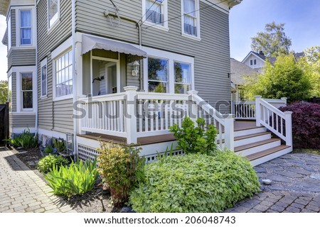 House with walkout deck. View of flower bed and brick tile walkway