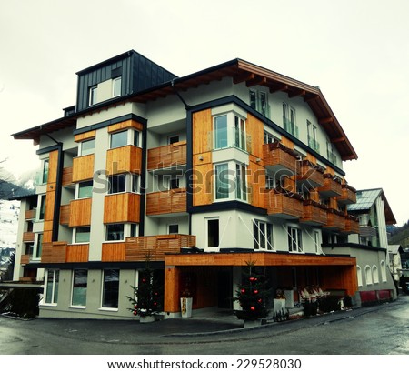 House with wooden balcony in winter mountain village, Austria. Toned image - stock photo