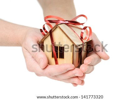 House Wooden in both hands with red ribbon - isolated on white background - stock photo