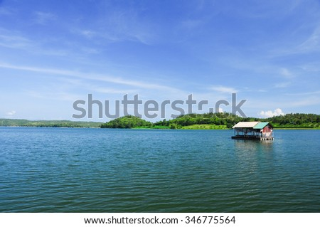 Houseboat floating on the lake over the dam under cloudy sky in Thailand
