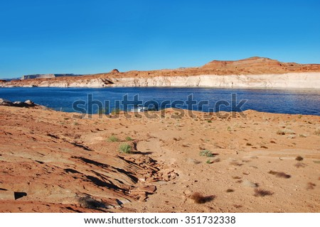 Houseboat is docked along the beautiful sandstone rocks and cliffs of the Glen Canyon National Recreation Area in Arizona.   - stock photo