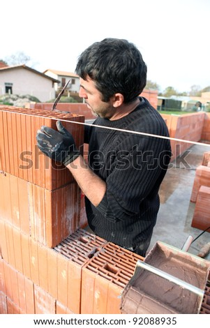 Housebuilder at work - stock photo