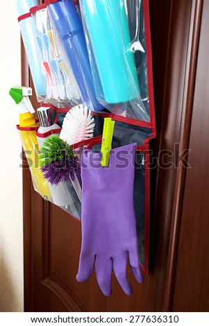 Household chemicals in holder hanging on wooden door background - stock photo