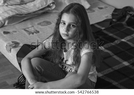 Household portrait. Portrait of a child girl. Girl child sitting on the bed with her hair down, sad.