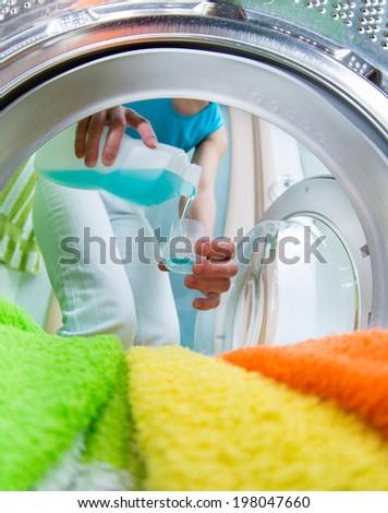 householder woman using conditioner for  washing machine - stock photo