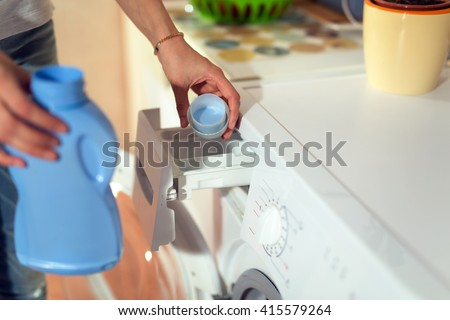 Householder woman using conditioner for washing machine - stock photo