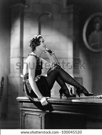 Housekeeper sitting on a desk and talking on the telephone - stock photo