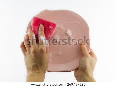 Housekeeping concept. Female hand with red sponge washing pink plate isolated on grey background