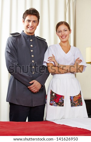 Housekeeping maid and happy concierge in a hotel room