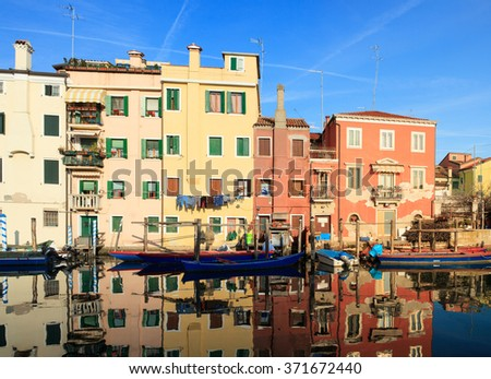 Houses and fisherboats reflected on the canal in Chioggia - stock photo