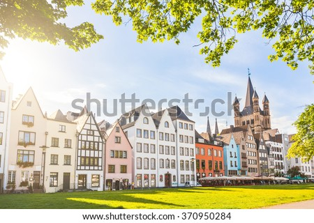 Houses and park in Cologne, Germany. Many of them are colourful, they are facing a public park with green grass and some trees. There is a bell tower on background. Travel and architecture concepts. - stock photo