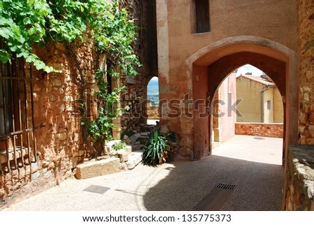 Houses behind an arc in historical ocher village of Roussillon, Provence, France